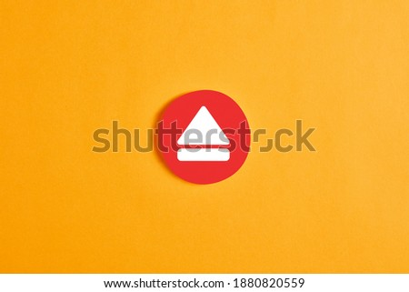 Photo of  Red round circle with an eject button or icon against yellow background.