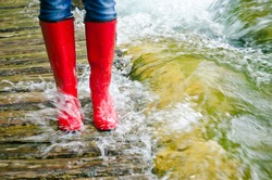 red rubber boots in water on a wooden bridge, the river overflowed its banks.
