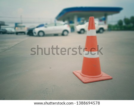 Red rubber cone on concrete floor in gas station, blurred background image #1388694578
