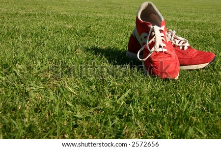 Red running shoes with white laces on a green sporting field #2572656