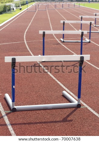 red running tracks with three hurdles set up for training
