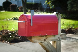 Red rural mailbox on a wooden post with flag up