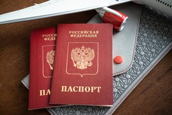 Red Russian foreign passports, next to the wing of a model airplane. Preparing for the trip.