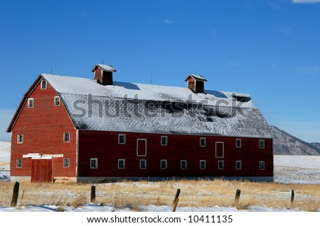 Red, rustic, wooden barn sits in an open field.  Mountain in background and vivid blue sky.