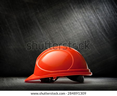 Red safety helmet on steel scratchy background