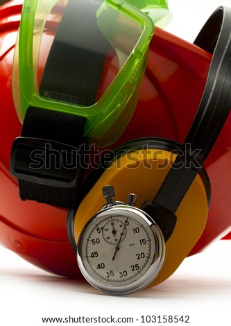 Red safety helmet with earphones, goggles and stopwatch