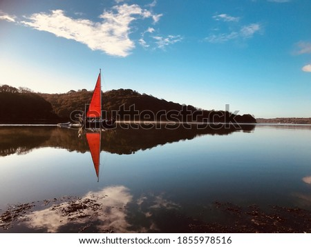 Red sail approaches Turnaware Point: Site of US embarkations for Day in 1944.  River Fal  in Cornwall.  Stock fotó ©