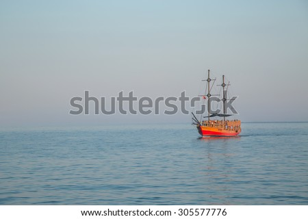 red sailboat sailing ship in the ocean gradually and proudly in the distant sky