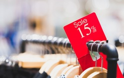Red sale sign 15% discount on clothing rack in modern shopping mall or department store with copy space. Retail shop promotional event, new product discount, or business marketing advertising concept