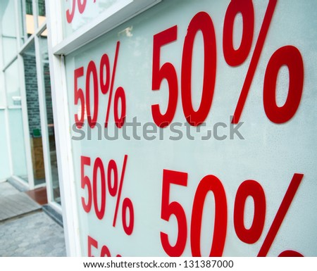 Red sale signs on shop wall, big reductions.