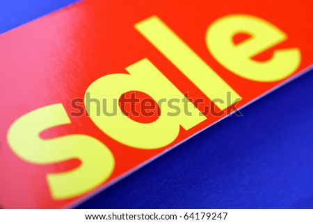 Red sale tag against a blue background with copyspace