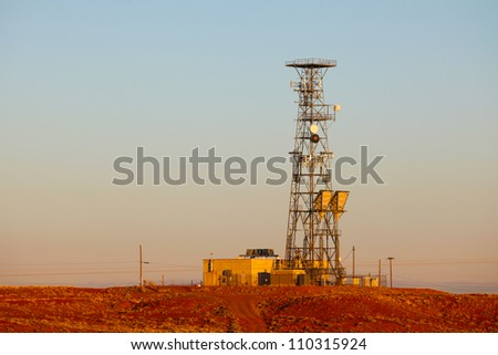 Red Sand Blue Sky/Long view of transmission tower along Route 66 amid reddish sands of New Mexico desert.