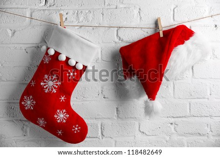 Red Santa Claus hat and sock hanging on white brick wall