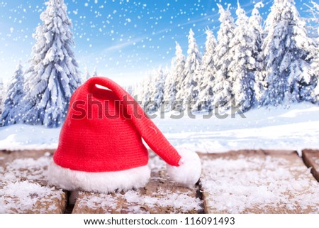 red Santa Claus hat on a wooden table with snow outside with an amazing winter wonderland in blurred background, forest in winter