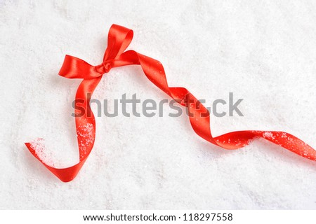Red satin gift bow. Ribbon on snow