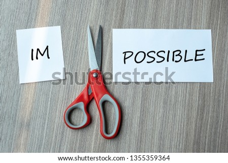 red scissors and cutting white paper with the text IMPOSSIBLE, change word to POSSIBLE. challenge, positive thinking and success concept #1355359364
