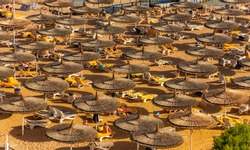 Red sea beach from aerial top view. Tourists relaxing under umbrellas on luxury resort, Egypt.