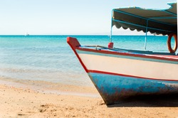 red sea with a wooden old and broken white blue boat on beach on warm sunset on jordan
