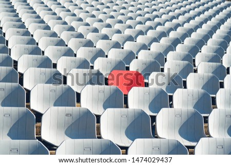Red seat in White seats on the stadium #1474029437
