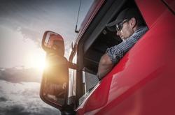 Red Semi Truck. Caucasian Truck Driver Preparing For the Next Destination.