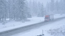 Red semi truck hauls a heavy cargo container across the state of Washington and through a snowstorm. Freight lorry navigates the slippery country road in the low visibility during an intense blizzard.