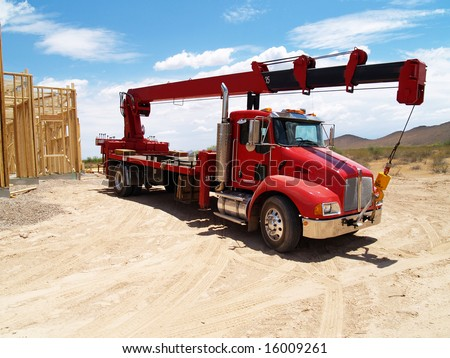 Red semi truck with a crane on it in a construction site with a house frame in the background. Horizontally framed photo.