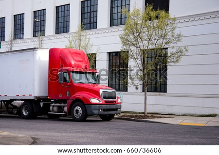 Red semi truck with short day cab and high spoiler to improve aerodynamic of rig with dry van trailer delivering goods by urban city street with contemporary buildings