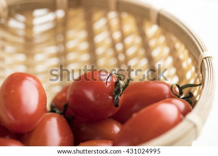 Red shiny cherry tomatoes placed in baskets. Isolated over white background