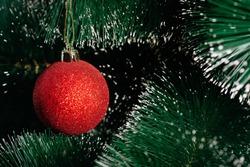 Red shiny Christmas ball on a Christmas tree with a snow. Christmas decor. Close-up