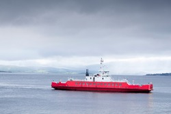 Red ship ferry transport over sea under dark storm clouds