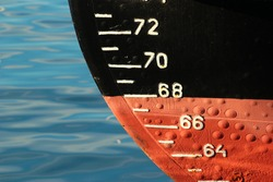 Red ship hull with waterline and draft scale measure
