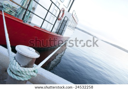 Red ship moored at a quay, focus on bitt and mooring lines.