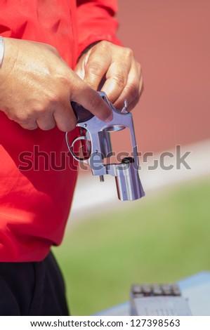 Red shirt man reloading ammo to silver gun
