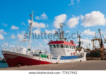 red shrimp trawler in the harbor and blue sky