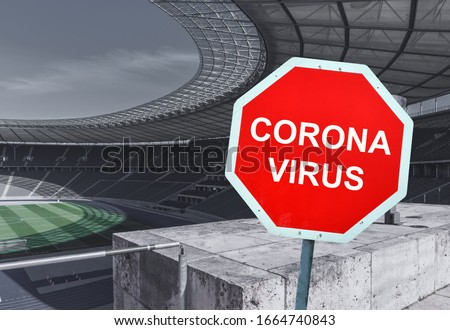 Red sign warning of coronavirus in stadium. Concept for euro soccer football sport event cancellation. Purposely blurred stadium in the background