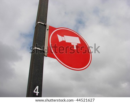 red sign with security camera