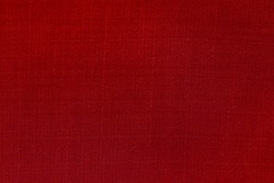Red silk fabric texture background for Christmas and New Year festive. Surface of red textured cloth as backdrop and wallpaper.