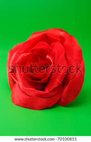 red silk rose for design on green