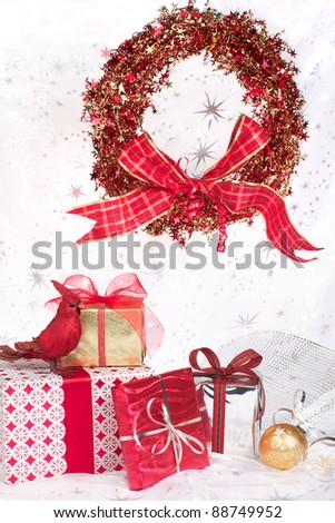 Red, silver, and gold wrapped Christmas gifts with pretty ribbons, wreath, and ornaments. Silver star translucent fabric backdrop on white. Vertical format with copy space.