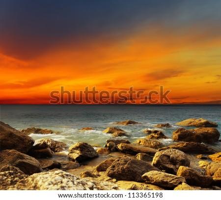 Red sky over a rocky seashore. Sunset landscape. #113365198