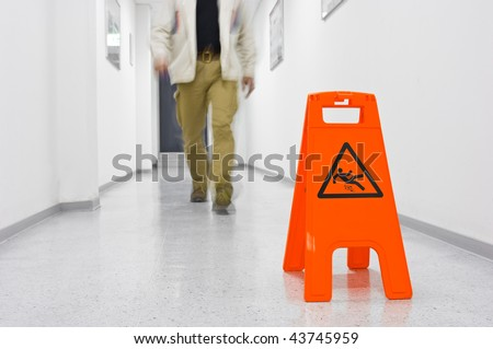 Red Slippery hazard sign in a corridor with legs of a walking person