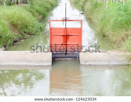 Red sluice in the ditch for drainage system.