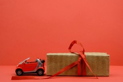 Red small car toy near the unpacked box with a red ribbon. Red background. Gift, surprise concept. Buy car concept. Copy space.