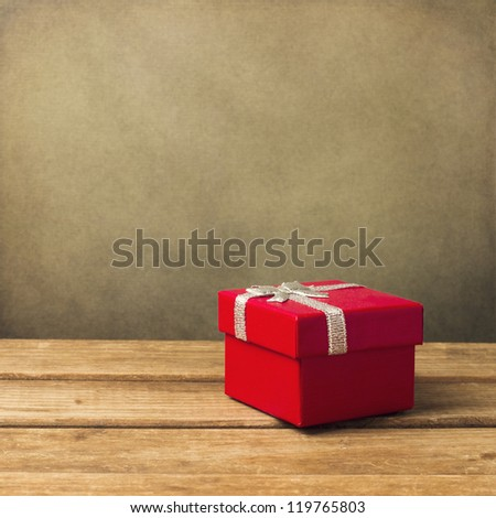 Red small gift box on wooden table over grunge background - stock photo