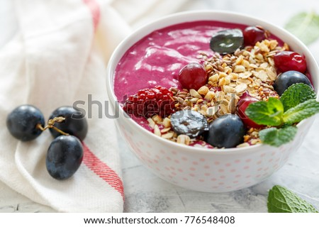 Red smoothie bowl with beets, granola, flax seeds and black grapes for tasty and healthy breakfast, selective focus.