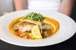 Red snapper fillet with mashed chickpeas, grilled peppers, boiled chickpeas and herb leaf.