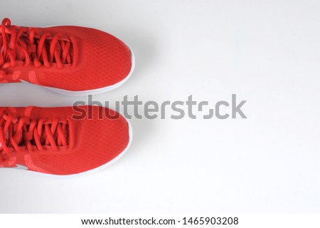Photo of Red sneakers on a white background. View from above. Free space to place text.