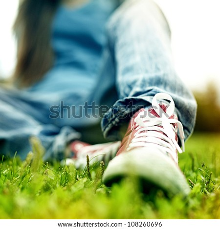 red sneakers on girl legs on grass during sunny serene summer day.