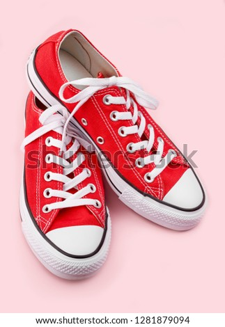 Red sneakers Red sneakers on pink background with copy space. Youth shoes.