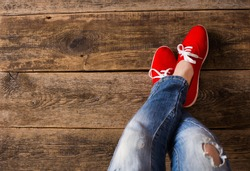 red Sneakers shoes walking on Dirty wooden top view